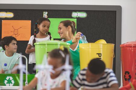 Vorderansicht des Lehrers, der mit Schulkindern über grüne Energie im Klassenzimmer diskutiert