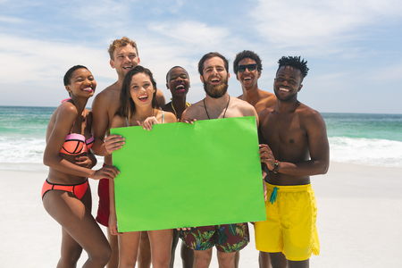 Portrait of happy multi-ethnic group of friends holding a empty green placard at beach on a sunny day. They are smiling and looking at camera Imagens