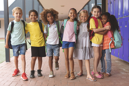 Front view of happy school kids standing in corridor and holding together in arms