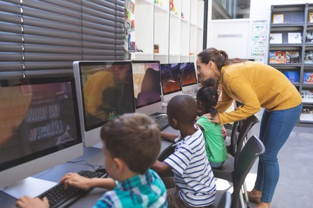 Side view of happy caucasian teacher teaching African-american schoolgirl while others students working on computers  in computer room