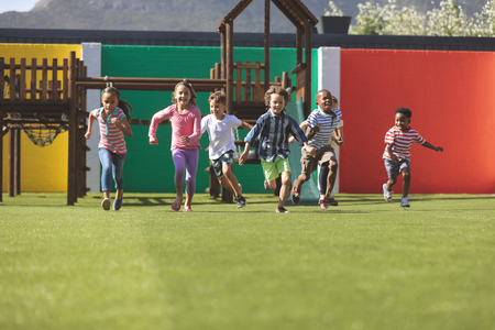 Front view of multi ethnic students running in school playground
