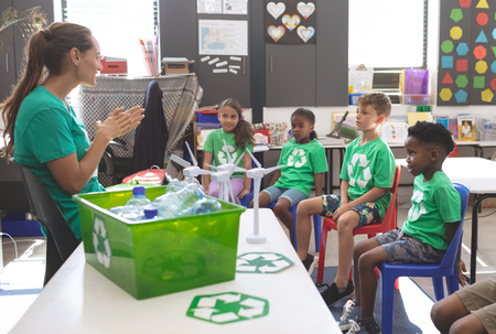 Side view of teacher interacting with school kids about green energy and recycle at desk in classroom at school 写真素材