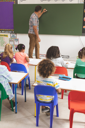 Rear view of teacher writting on greenboard with a piece of chalk with school kids sitting on their chairs in foreground in classroom at school