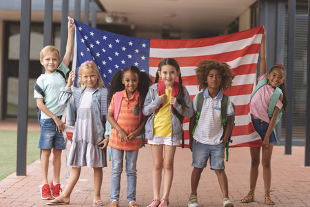 Front view of happy school students standing in outside corridor at school while holding american flag