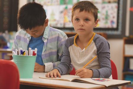 Vorderansicht kaukasischer Schulkinder, die im Klassenzimmer in der Schule auf Notebook zeichnen Standard-Bild