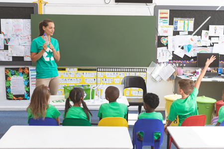 Front view of caucasian teacher holding plastic bottle and standing in front of multi ethnic students discussing about green energy and recycle at desk in classroom