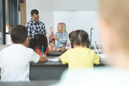 Front view of a Caucasian schoolgirl explaining to others school kids the human body with his teacher next to her Stock Photo