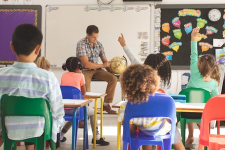 Front view of schoolteacher learning at his pupils the earth globe in classroom at school with school kids looking at him and raising hand in foreground