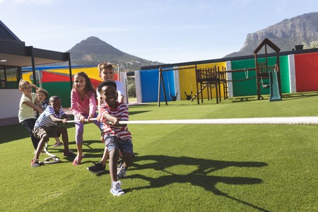 Front view of multi ethnic group of happy school kids playing tug of war in playground