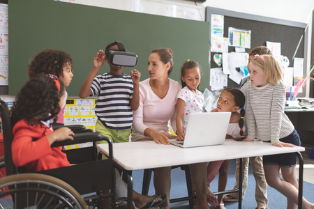 Front view of schoolboy using virtual reality headset at school in classroom 版權商用圖片