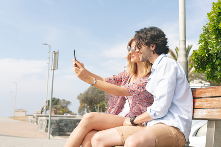 Side view of young Caucasian couple taking selfie with mobile phone while sitting at bench on a sunny day. They are smiling