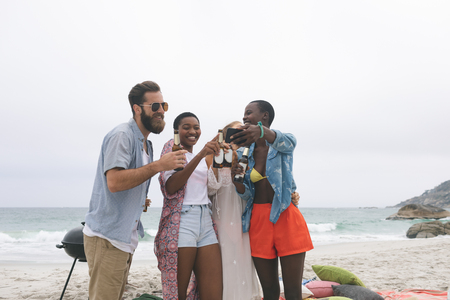 Front view of multi ethnic group of friends reviving photo on mobile phone at beach while drinking beer