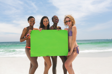 Portrait of happy multi-ethnic female friends holding a empty green placard at beach on a sunny day. They are looking and smiling at camera