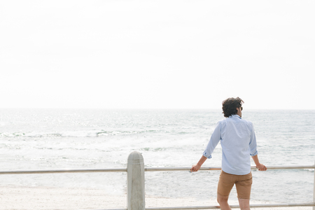 Rear view of youg Caucasian man standing near sea side at promenade on a sunny day. He is looking away