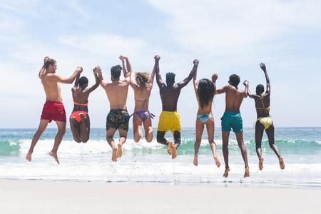 Vista posteriore di diversi amici di gruppo che si divertono e saltano in acqua in spiaggia in una giornata di sole