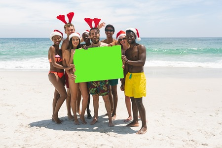 Front view of happy multi-ethnic group of friends with Christmas hat holding a empty green placard at beach on a sunny day. They are smiling and looking at camera Imagens