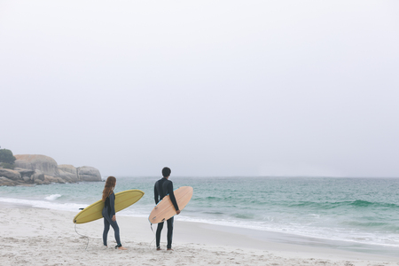 Rear view of young multi-ethnic couple surfer holding surfboards on the beach. They are looking the waves