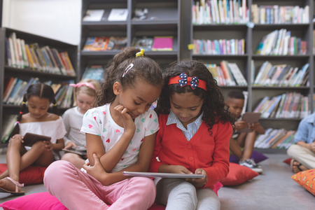 Widok z poziomu powierzchni dwóch zrelaksowanych uczennic patrzących na cyfrowy tablet, podczas gdy inne dzieci w wieku szkolnym robią to samo w tle w bibliotece