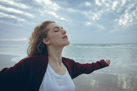Side view of beautiful young Caucasian woman with curly hair standing arm stretched at beach while closing eyes. She is relaxed Imagens