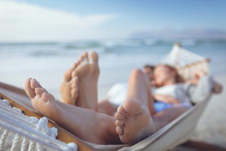 Nahaufnahme von entspannten kaukasischen Paarfüßen, während sie an einem sonnigen Tag auf der Hängematte am Strand schlafen
