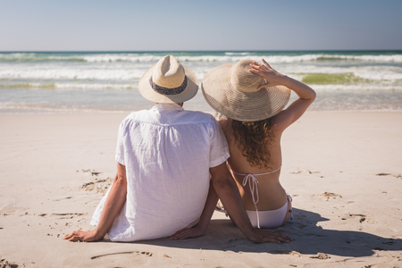Rear view of young Caucasian couple relaxing sittingface to the sea at beach on a sunny day. They wear hats Reklamní fotografie