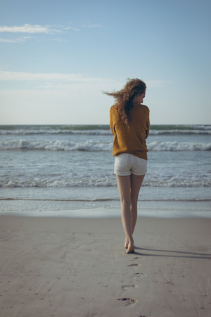 Rear view of young Caucasian woman walking barefoot on the sand at beach on the sunny day