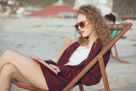 Front view of beautiful young Caucasian woman with sunglasses reading book while sitting on sun lounger at beach on sunny day. Standard-Bild