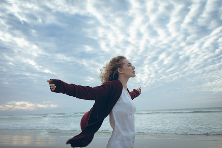 Side view of beautiful young Caucasian woman with curly hair standing arm stretched at beach. She is relaxed