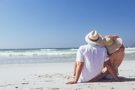 Rear view of young Caucasian couple relaxing sitting face to the sea at beach on a sunny day. They wear hats