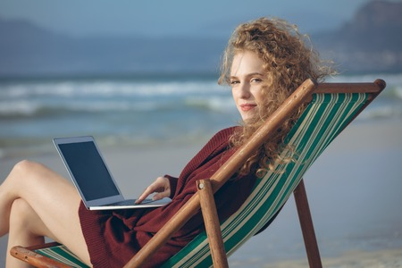 Portrait of beautiful young Caucasian woman using laptop while sitting on sun lounger at beach. She is smiling and looking at camera