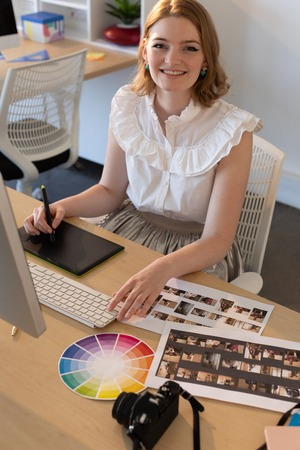 Ritratto di giovane graphic designer femminile caucasica che lavora su tavoletta grafica e computer alla scrivania in ufficio. Sta sorridendo e guardando la telecamera