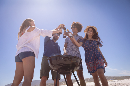 Low angle view of group of  Multi ethnic friends toasting beer bottle at beach in the sunshine surrounding of barbecue 版權商用圖片