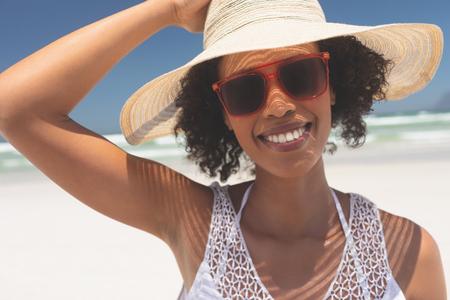 Portret pięknej młodej kobiety rasy mieszanej, uśmiechając się i patrząc na aparat stojący na plaży w słoneczny dzień. Nosi kapelusz i czerwone okulary przeciwsłoneczne