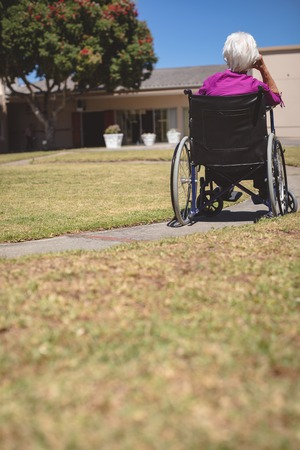 Rear view of senior Caucasian woman relaxing on wheelchair at nursing home park Imagens