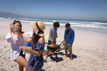 Front view of two Multi ethnic women friends dancing while men friends doing a barbecue with ocean waves in background Standard-Bild