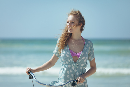 Front view of beautiful young Caucasian woman holding bicycle at beach on a sunny day. She is looking away