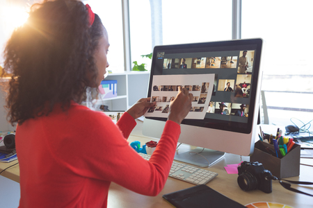 Rear view of beautiful African American female graphic designer looking at photographs at desk in a modern office Banco de Imagens