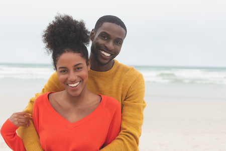 Portrait of Multi-ethnic couple standing at beach on a sunny day. They are smiling and looking at camera