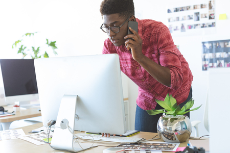 Side view of young African-American graphic designer talking on mobile phone while working on computer at desk in office