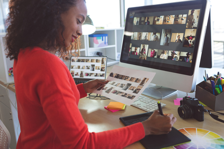 Side view of pretty African American female graphic designer writing on tablet while holding A4 paper with photographs at desk in a modern office