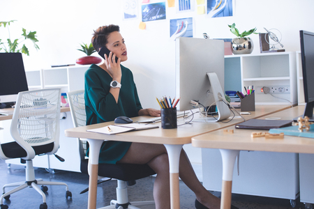 Side view of beautiful Mixed-race female executive talking on mobile phone at desk in the office Stock Photo