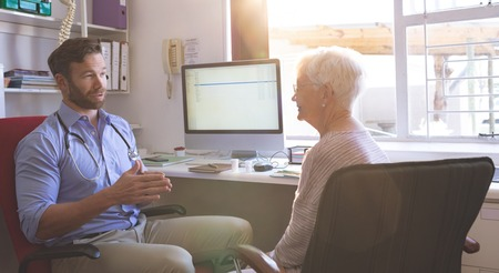 Side view of Caucasian male doctor and Caucasian senior woman interacting with each other in clinic