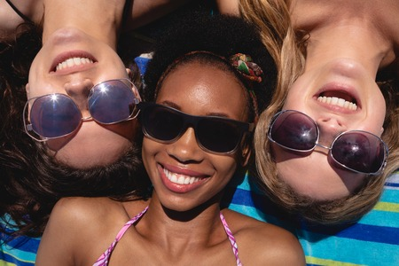 Close-up of happy beautiful young multi ethnic women with sunglasses lying on beach in the sunshine Stockfoto