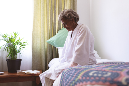 Side view of senior mixed race woman sitting upset in nursing home Stock Photo - 121755119
