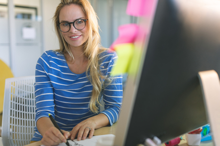 Portrait of young Caucasian blonde female fashion designer looking and smiling at camera while drawing sketches at desk in a modern office