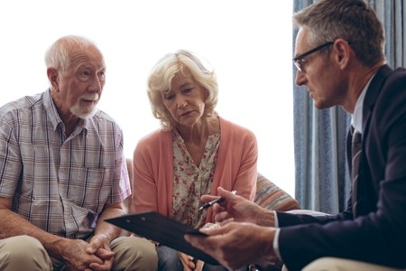 Side view of matured Caucasian male physician interacting and showing papers to senior Caucasian couple at retirement home
