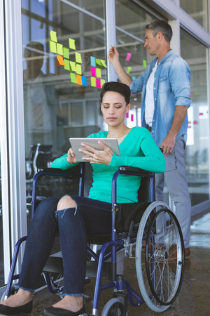 Front view of disabled Mixed-race female executive using digital tablet while Caucasian male executive writing on sticky notes in office