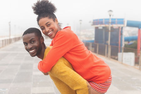 Portrait of strong African American man carrying Mixed-race woman piggyback at pavement. They are smiling and looking at camera