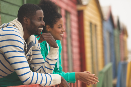 Side view of smiling Multi-ethnic couple interacting with each other while looking at the sea at beach hut
