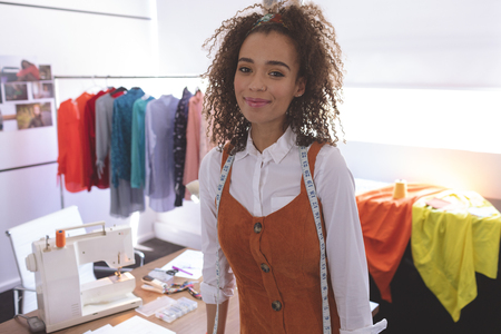 Portrait of young Mixed-race female fashion designer standing at table in design studio. She is smiling and looking at camera